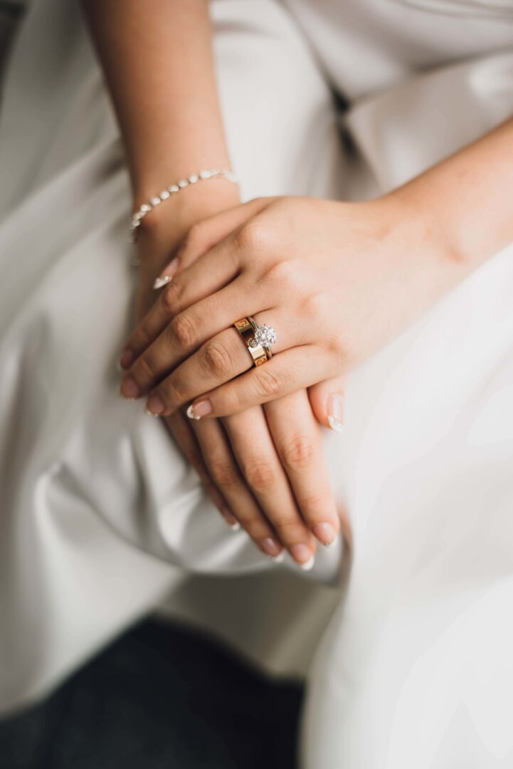 Diamond set of rings and bracelet on woman's hand.